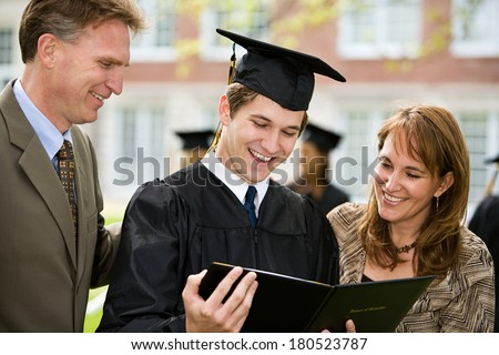 Graduation Male Student Stands Proudly With Parents