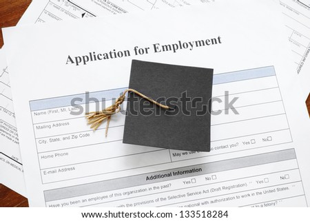 graduation mortar board cap on job application form - underemployent concept