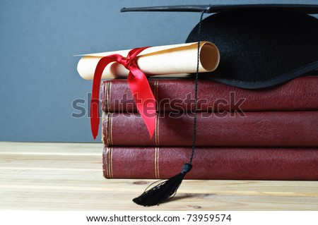 Graduation mortarboard and scroll tied with red ribbon on top of a stack of old, worn books on a light wood table.  Grey background.