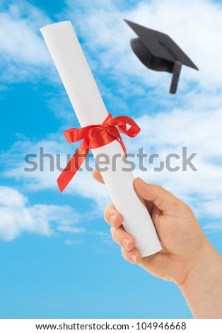 Graduation scroll held into the sky with mortar board