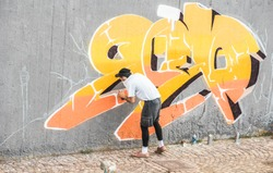 Graffiti artist covering his face while painting with color spray on the wall - Urban, street art, millennials generation, mural concept - Focus on his head