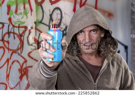Graffiti artist in a gray dress with hood spray paint for picture on