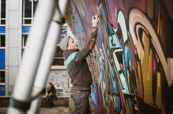 Graffiti artist painting with aerosol spray on the wall