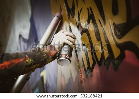 Graffiti artist painting with aerosol spray on the wall