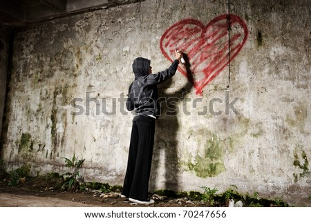 Graffiti artist paints a love valentine heart on grunge wall