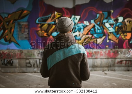 Graffiti artist standing near the wall