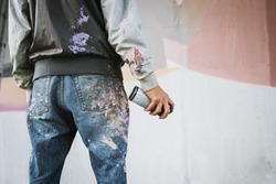 Graffiti artist with aerosol spray bottle near the wall