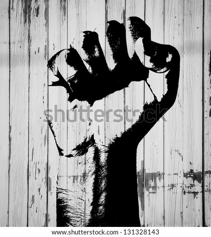 Graffiti fist.Retro style clenched fist held high in protest against wooden panels