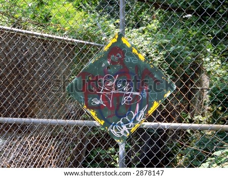 Graffiti on sign with chain link fence
