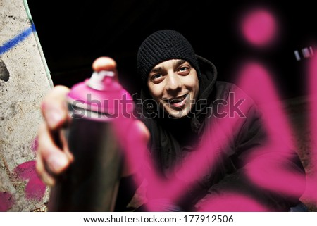 Graffiti painter drawing a picture on the wall. stock photo
