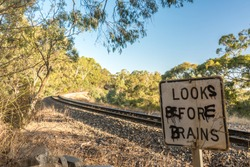 Graffitied warning sign at a railway crossing, Belair National Park, Adelaide, Australia