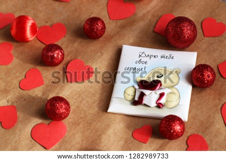 "Graft paper background with a cute bear on it. Bear with Russian words ""Giving my heart to you"" on it. Red hearts and red balls. Valentine's Day- concept. #1282989733"