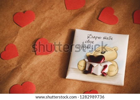 """Graft paper background with card a cute bear on it. Bear with Russian words """"Giving my heart to you"""" on it. Red hearts. Valentine's Day- concept. #1282989736"""