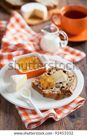 Grain Irish soda bread slice, brie cheese and jam on plate, selective focus