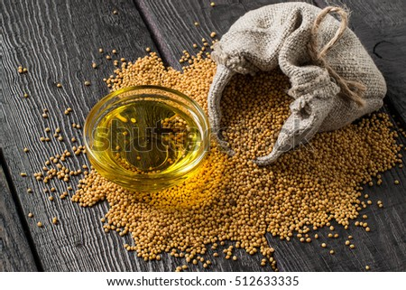Grain mustard in a linen bag and mustard oil in a glass bowl. It is used in dietary and healthy nutrition, cosmetics, herbal medicine. The source of vitamins and polyunsaturated fatty acids #512633335