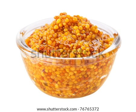 Grain mustard in transparent glass bowl, isolated on white