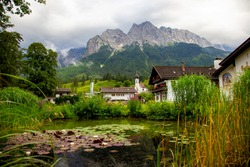 Grainau, bavarian village. domed church St. Johannes, graveyard with Mountains (Waxenstein and Zugspitze peaks). Wetterstein range Northern Limestone Alps Bayern Germany Europe. Pond in the foreground