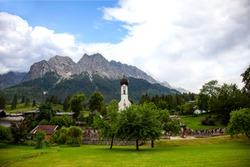 Grainau, bavarian village. domed church St. Johannes, graveyard with Mountains (Waxenstein and Zugspitze peaks). Wetterstein range Northern Limestone Alps Bayern Germany Europe.