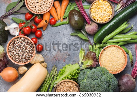 Grains in bowls and vegetables arranged in a circle with copy space in the middle, broccoli, squash, beans, tomatoes, carrots, avocado, quinoa, peas, rice, oats, selective focus
