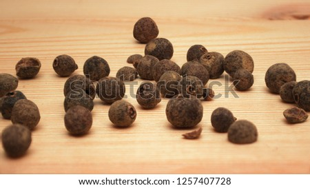Grains of allspice on a wooden background #1257407728