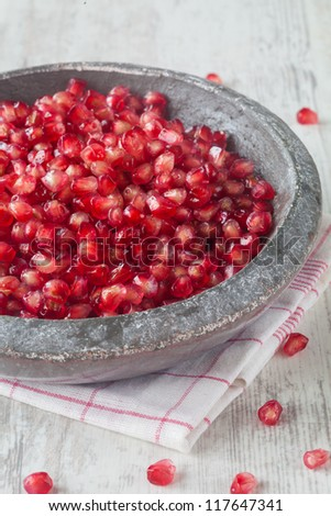 Grains of fresh pomegranate in a stone plate