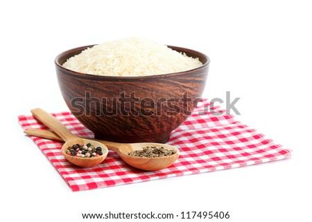 Grains of rice in a bowl and two wooden spoons with spices isolated on white background.