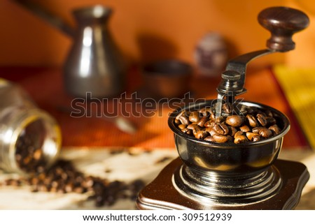 Grains of roasted Arabica coffee with coffee grinder, Turks, a glass jar on a bamboo mat and wooden table in natural light, the sun.