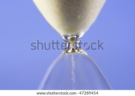 Grains of sand falling down in hourglass