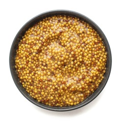Grainy mustard in dark bowl isolated on white background. Top view.
