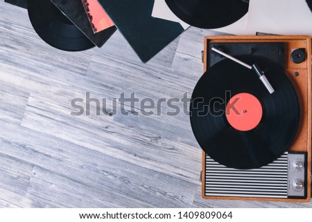 Gramophone vinyl record player on the background of their gray wooden boards. Needle on a vinyl record. Black vinyl record,Sound technology for DJ to mix & play music. #1409809064