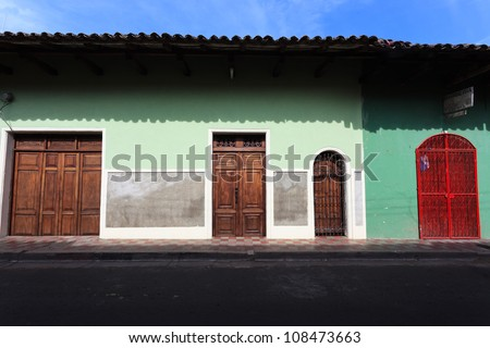 GRANADA, NICARAGUA: Facades of a row of colorful houses with carved wooden doors in the historic district of Granada
