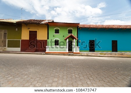 GRANADA, NICARAGUA: Row of colorful houses on cobblestone street in the historic district of Granada.