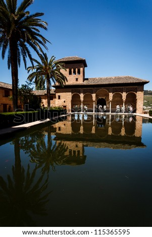 GRANADA, SPAIN - APRIL 27, 2010: the pavilion with arched portico by pool and tower and palm trees at the Palacio del Partal in Alhambra with Lion Patio reopened on April 27, 2010 in Granada, Spain.