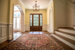 Grand and elegant yellow entrance to a home with stairs. Oriental rug a wood and glass window door.