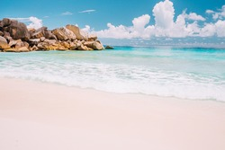 Grand Anse beach at La Digue island in Seychelles. Sandy beach with blue ocean bay, white clouds in background