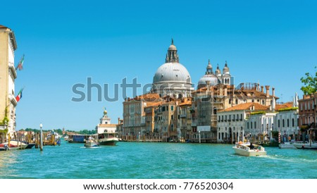 Grand Canal in Venice, Italy. Grand Canal is one of the main tourist attractions of Venice. Beautiful panoramic view of Grand Canal in summer. Panorama of Venezia with Grand Canal and Basilica domes. #776520304
