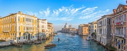 Grand Canal in Venice, Italy. Wide view of the main street panorama of the major street of Venice with motor boats with beautiful picturesque clouds in the sky. Basilica di Santa Maria della Salute