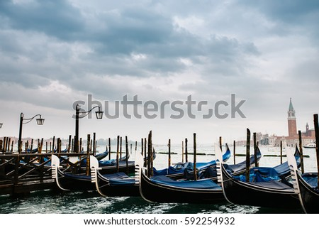 Grand canal in Venice, Piazza San Marco, in the background the island San Giorgio. Beautiful moody cityscape with gondolas. #592254932