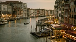 Grand Canal with gondolas at night, Venice, Italy. Panoramic view of the famous Grand Canal in twilight. Romantic water trip across Venice in evening. Nice panorama of Venice waterfront at dusk.