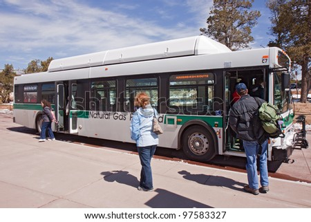 GRAND CANYON, AZ - MARCH 23: Visitors board a south rim shuttle bus at Grand Canyon Visitor's Center on March 23, 2011. The free buses are powered by compressed natural gas and reduce park traffic.