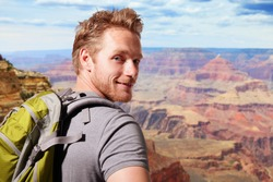 Grand Canyon travel  - Successful man mountain hiker with backpack on the top of mountains. caucasian