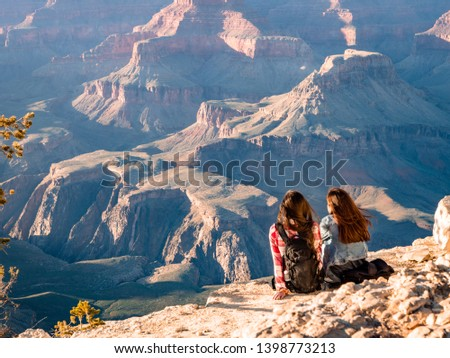 GRAND CANYON, USA - APRIL 15, 2019: Two young Girls sat enjoying the amazing views of the Grand Canyon #1398773213
