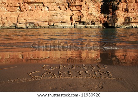 Grand Canyon written in the sand on a Colorado River bank beach across from a cliff