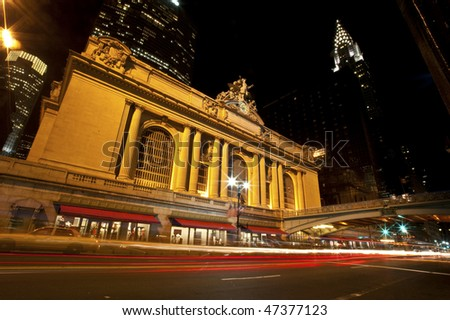 Grand Central Station lit up at night, with blurs of passing cars.