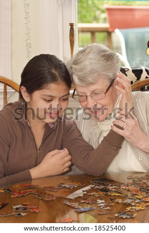 Grand daughter and grand mother with faces close together working on jigsaw puzzle on kitchen table