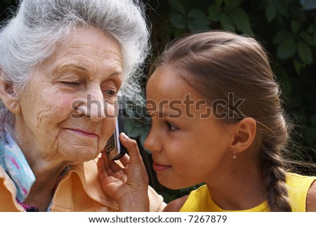 Grand daughter and her grand mother talk on mobile phone - stock photo
