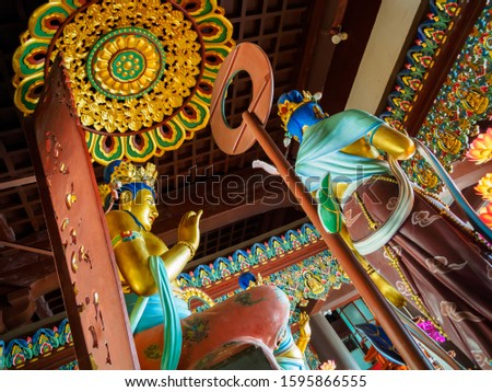 Grand gold painted statue of Buddha with elaborate carvings at Nanshan temple in Hainan, China.