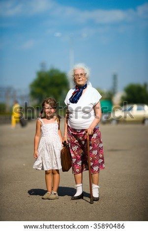 Grand grandmother and little girl together summer outdoors