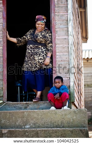 Grand mother and her son together on the porch of their house.
