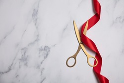 Grand opening background. Gold scissors with red ribbon on a marble background